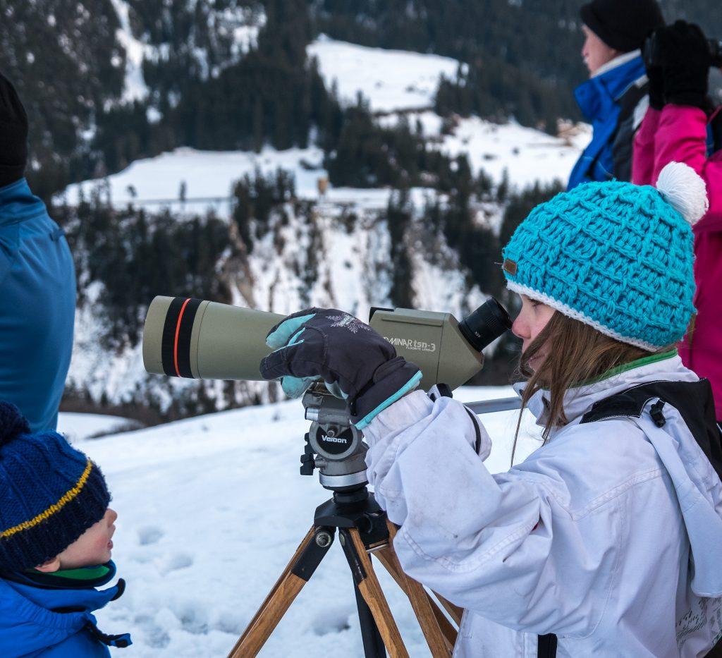 Aimee bestaunt die in Graubünden wild lebenden Hirsche durch das Fernrohr